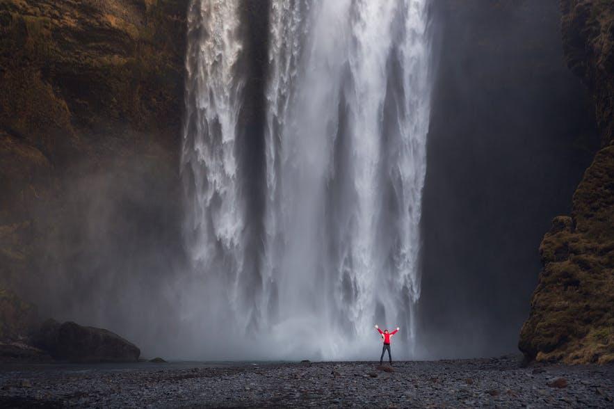 Một nhân vật áo đỏ đứng ở tiền cảnh của thác nước tạo sự thu cho bố cục cho bức ảnh